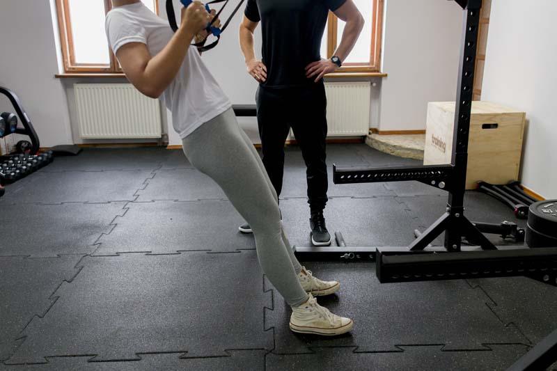 Kobieta wykonująca trening funkcjonalny z pomocą trenera personalnego