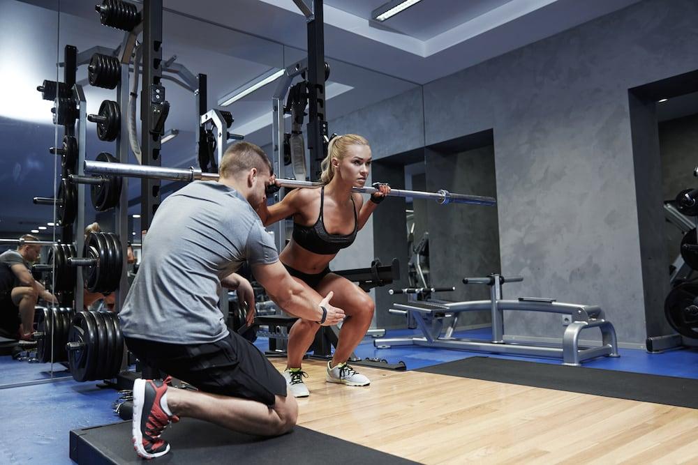 Kobieta wykonująca trening odchudzający z pomocą trenera personalnego